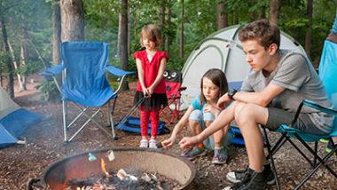 Kids camping and roasting marshmallows