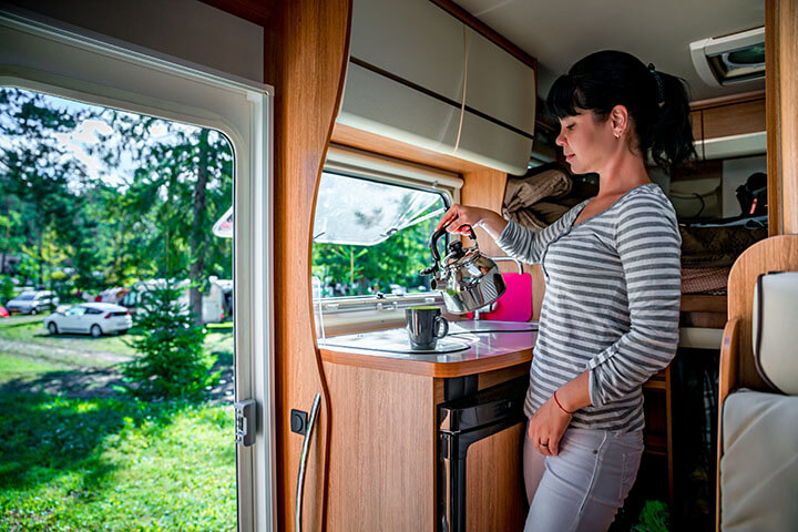 Woman cooking and using appliance in an RV
