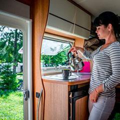 woman-cooking-in-camper-motorhome-interior-rv